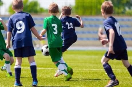 Kinderen spelen voetbal met elkaar