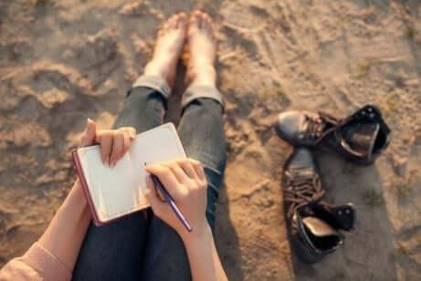 Een vrouw schrijft in een notitieboek op het strand