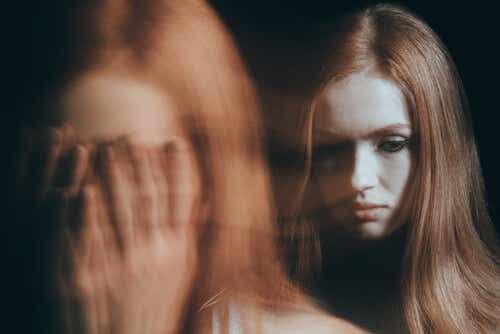 Een vrouw met haar handen voor haar gezicht in wazig beeld met een duidelijker beeld van dezelfde vrouw erachter