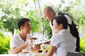 Een lachend stel aan tafel krijgt de rekening van een ober