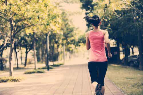 Een vrouw loopt hard door een straat met bomen langs het pad
