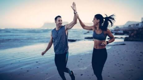 Een man en een vrouw geven elkaar een high five op het strand