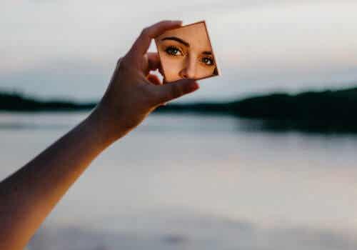 Het gezicht van een vrouw in een kleine make-upspiegel