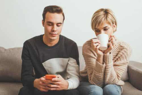 Een koppel zit op de bank, de man speelt met zijn telefoon terwijl de vrouw uit een beker drinkt
