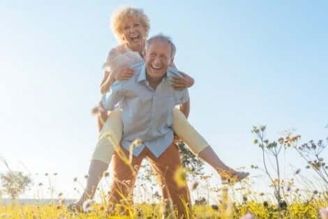 Een oudere man draagt zijn oudere vrouw op de rug terwijl ze lachen