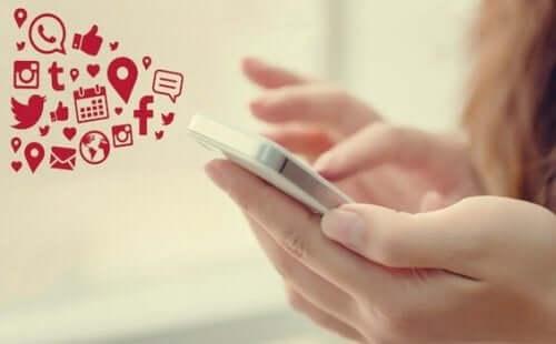 Een mobiele telefoon met de logo's van verschillende sociale media platvormen erbij