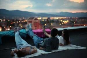Drie vrienden zitten op de rand van een dak van een hoog gebouw