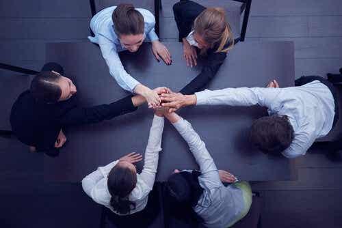 Mensen staan in een kring met de handen op elkaar