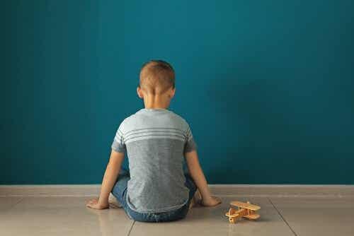 Een jongetje zit met zijn rug naar de camera