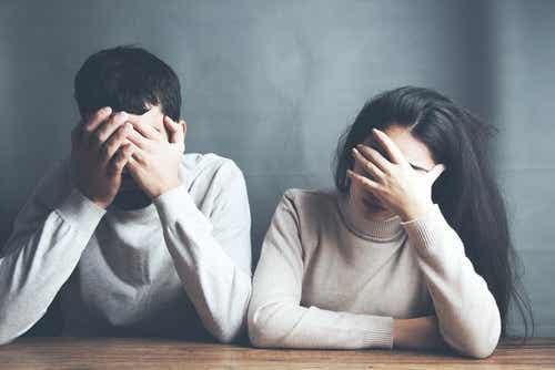 Een man en een vrouw houden hun handen voor hun gezicht