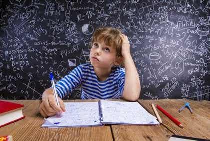Een jongen zit aan een bureau met een schrijfblok en een pen