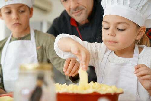 Kinderen met schorten en een koksmuts zijn aan het koken