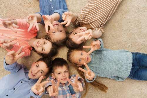 Een groep kinderen maakt het vredesteken met hun vingers
