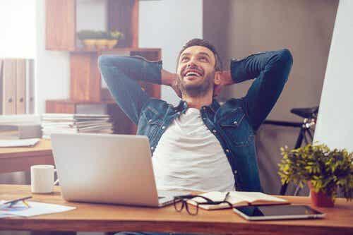 Een man zit achter een computer en lacht