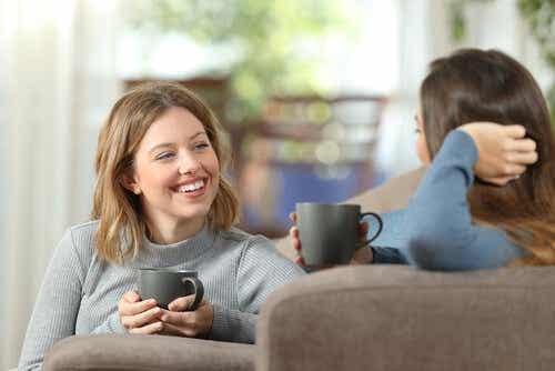 Twee vrouwen praten met een kop koffie in hun handen