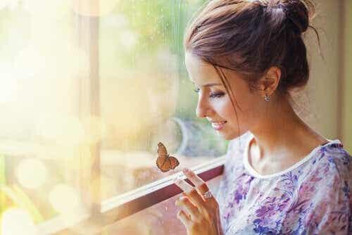 Een vrouw kijkt naar een vlinder die op het raam zit