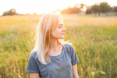 Een vrouw staat in een grasveld met haar ogen dicht