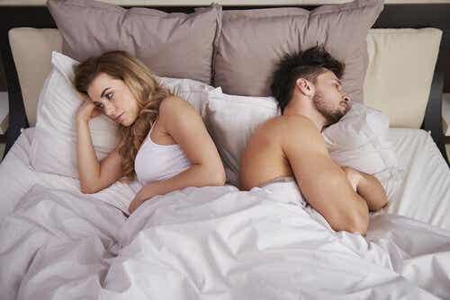 Een man en een vrouw liggen in bed met de ruggen naar elkaar toe