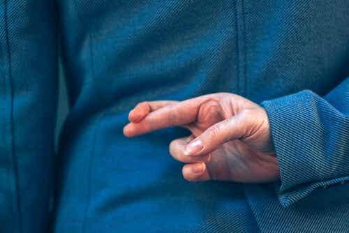 Een man houdt zijn vingers gekruist achter zijn rug