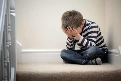 Een kind zit huilend op de trap