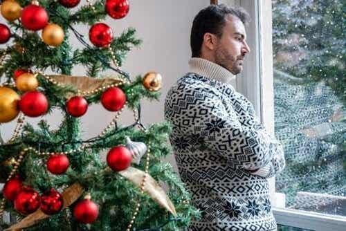 Een man staat boos bij een kerstboom