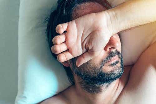 Een man wordt wakker met zijn hand voor zijn gezicht