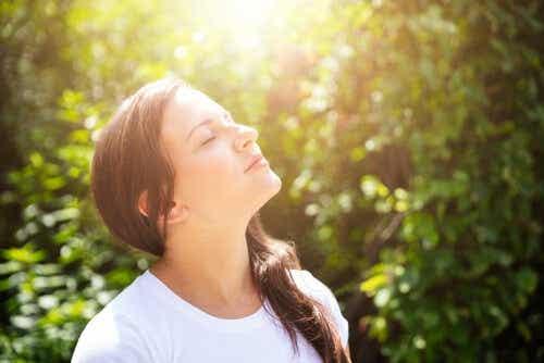 Een vrouw richt haar gezicht naar de zon