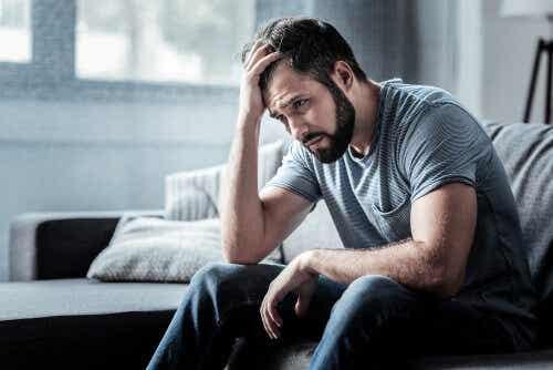 Een man zit op de bank met zijn hand in zijn haar