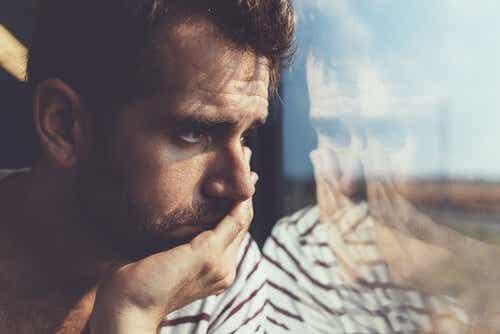 Een man kijkt uit een raam en voelt zich depressief