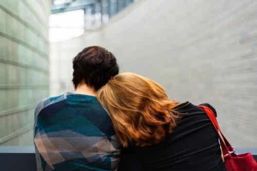 Een vrouw met haar hoofd op de schouder van een man