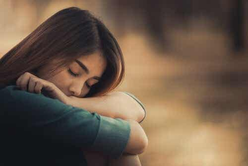 Een vrouw met haar hoofd op haar armen en de ogen gesloten