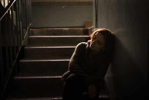 Een verdrietige vrouw leunt tegen de muur in een trappenhuis
