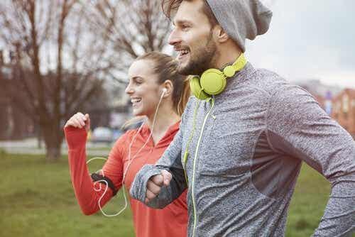 Twee mensen rennen met lachende gezichten door een park