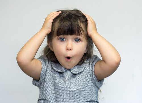 Een klein meisje met haar handen op haar hoofd kijkt verbaasd