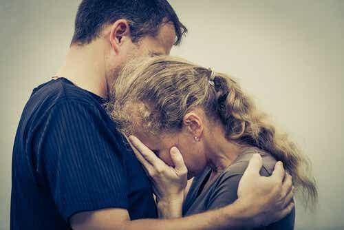 Een man omhelst een verdrietige vrouw