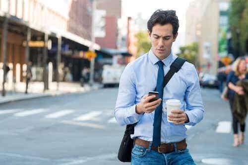 Een man loopt op straat en kijkt naar zijn mobiele telefoon