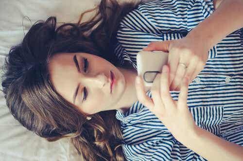 Een vrouw ligt op bed en kijkt naar haar mobiele telefoon