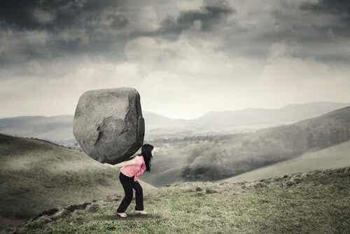 Een vrouw die een grote steen draagt