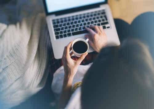 Een vrouw drinkt koffie en werkt op haar computer
